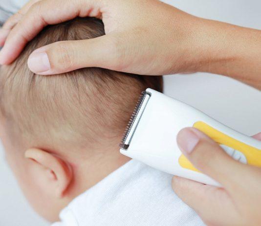 Mutter beim Baby Haare schneiden mit der Haarschneidemaschine