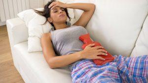 Frau liegt mit Schmerzen im Bett