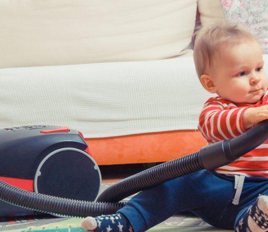 Baby spielt mit dem Staubsauger