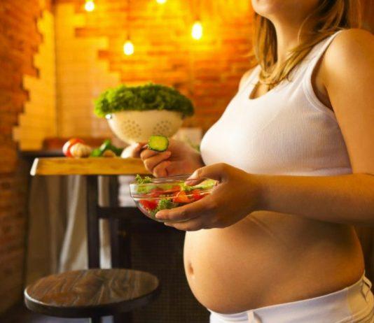 Scharf essen Schwangerschaft: Schwangere isst Radieschen im Salat