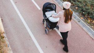 Mutter geht mit Baby im Kinderwagen spazieren