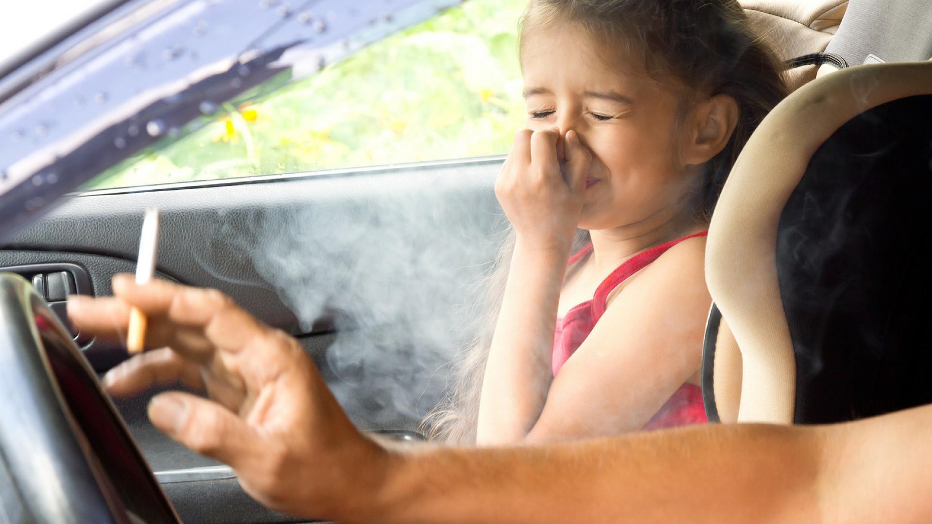 Vater raucht neben Tochter im Auto