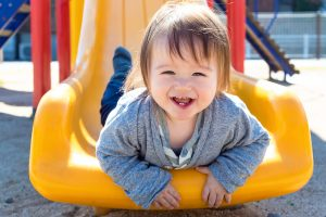 Kleiner Junge liegt auf der Rutsche und lacht