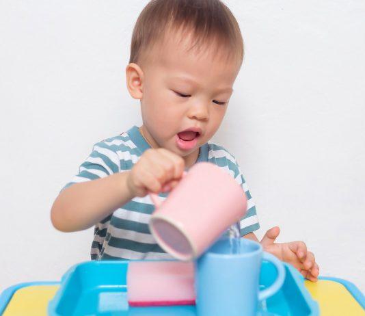 Junge spielt mit Bechern und Wasser