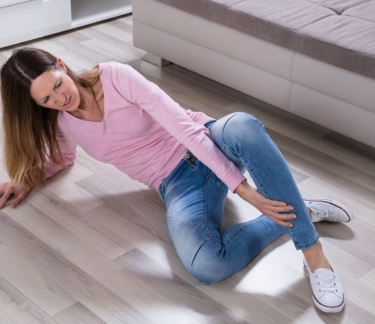 Frau liegt am Boden und hält ihr Bein