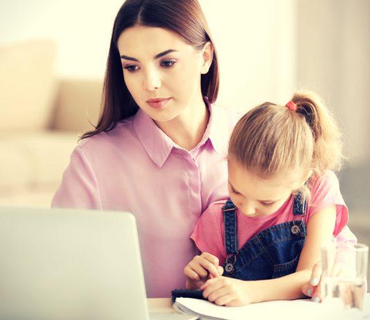 Mama sitzt mit ihrer Tochter vor dem Laptop
