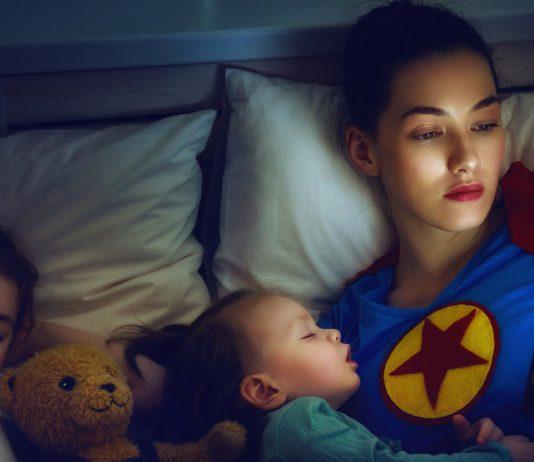 Superhelden Mama liegt mit ihren Kindern im Bett
