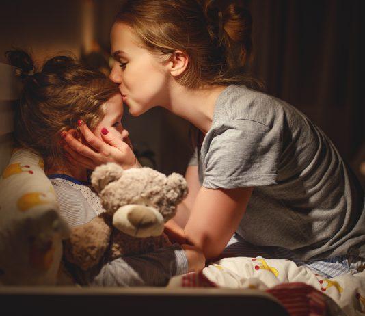 Mama bringt ihre Tochter liebevoll ins Bett