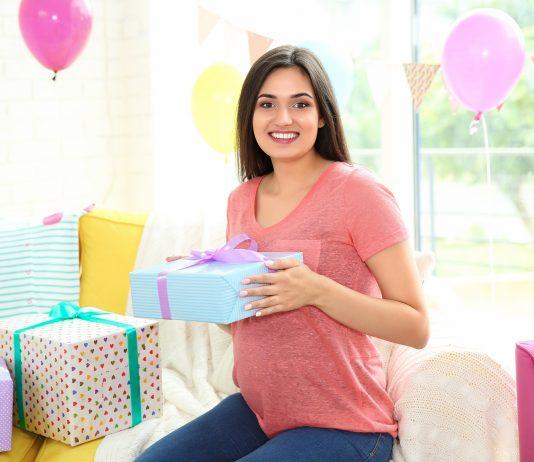 Schwangere Frau freut sich über ihre Geschenke
