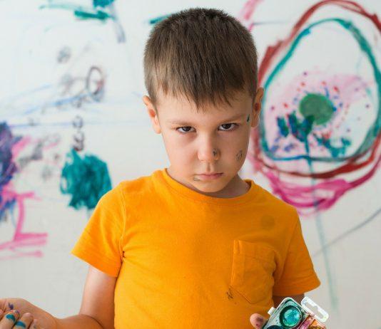 Junge hat die sauberen, weißen Wände bemalt