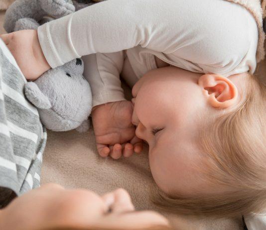 Baby schläft bei seiner Mama und seinen Kuscheltieren