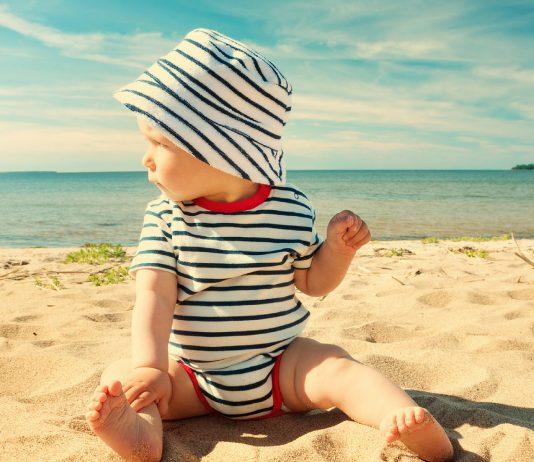Baby mit Sonnenhut am Strand