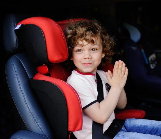 Junge sitzt im Auto in einem Kindersitz