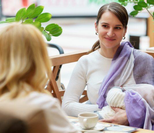 Frau stillt ihr Baby in einem Café