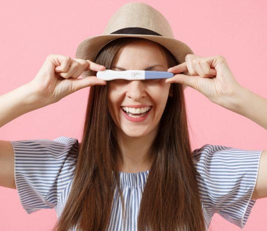 Frau freut sich über ihren Schwangerschaftstest