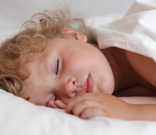 Kleinkind schlaeft im Kinderbett