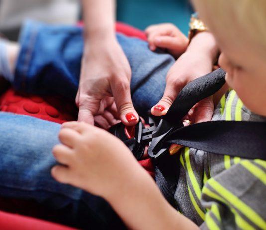 Junge wird im Kindersitz angeschnallt