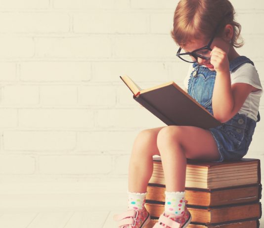 Kleines Mädchen liest ein großes Buch