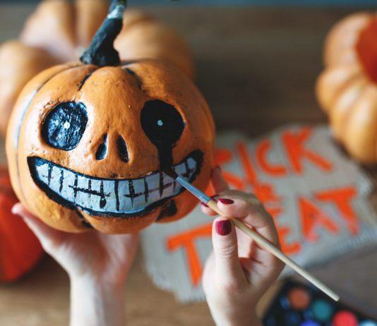 Halloween-Kuerbis wird bemalt