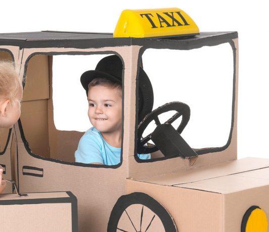 Kinder spielen mit einem Taxi aus Pappe