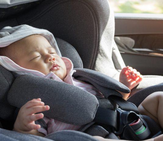 Asiatisches Baby schläft im Maxi Cosi