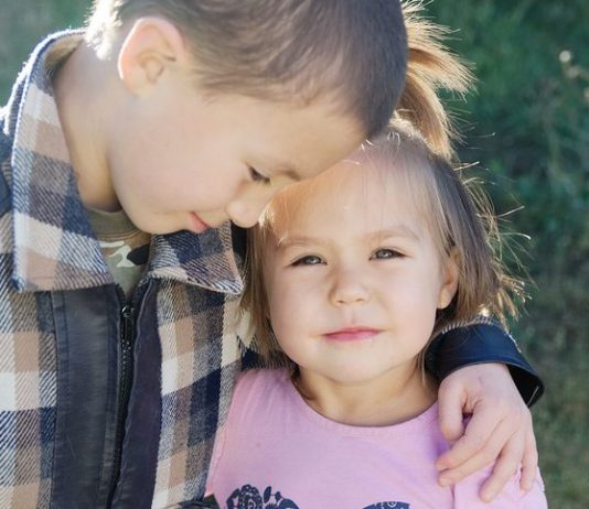 Großer Bruder umarmt seine kleine Schwester