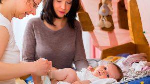 Hebamme und Mutter wickeln Baby