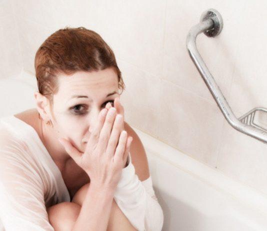Frau sitzt verzweifelt in der Badewanne.