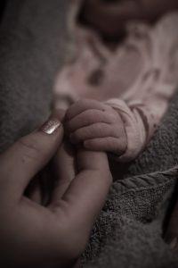Sternenkindfotos: Mutter haelt die Hand ihres Babys