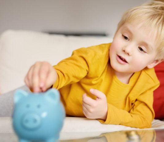 Taschengeld-Tabelle: Junge steckt Münze in Sparschwein