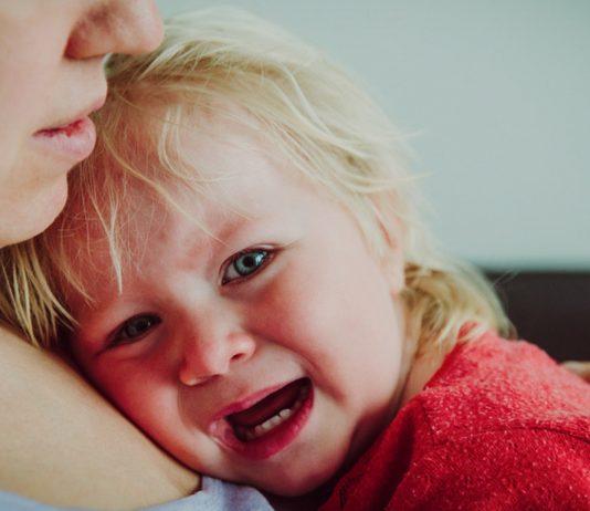 Kind weint aug Mamas Arm