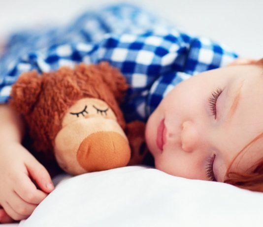 Junge schläft mit Teddy