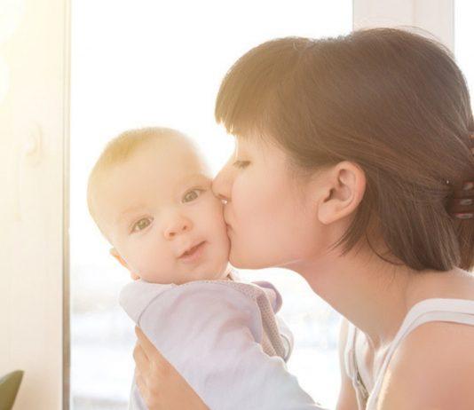 Mutter gibt ihrem Baby einen küss auf die Wange
