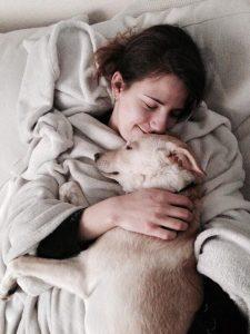 Marija kuschelt mit ihrem Hund Luke