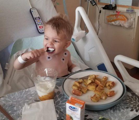 Junge isst am Krankenbett