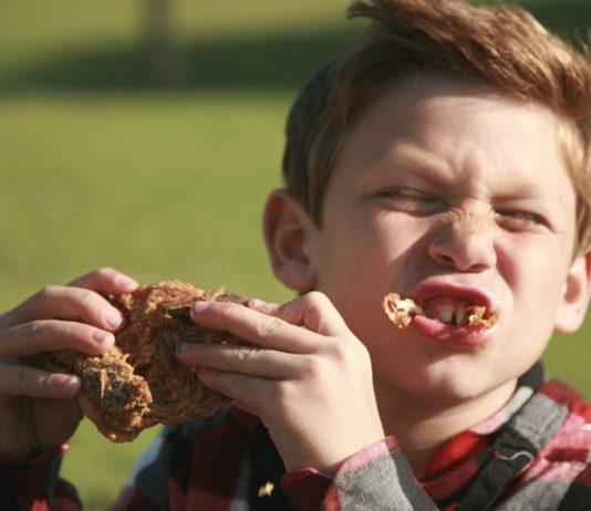 Junge isst Grillhähnchen