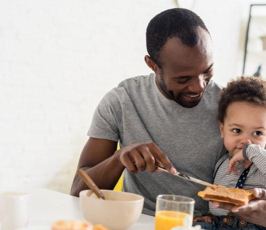 Vater frühstückt mit Baby
