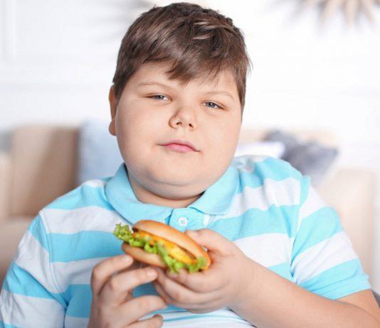 übergewichtiger Junge mit Burger in der Hand