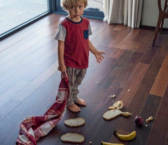 Kleinkind hat Essen auf dem Boden verteilt