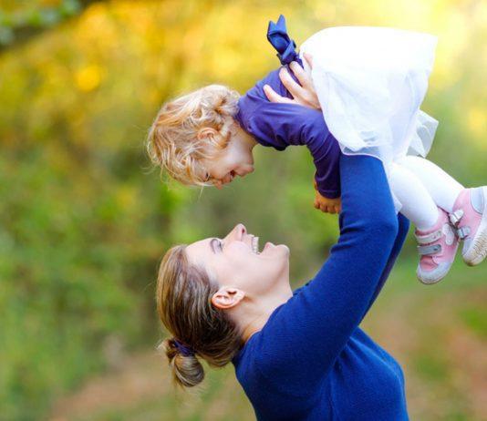 Greife nach den Sternen: Mutter hält lachende Tochter in die Luft