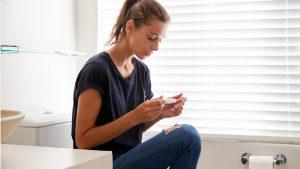 Frau möchte schwanger werden und schaut auf Schwangerschaftstest