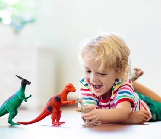 Kind spielt mit Dinosaurier