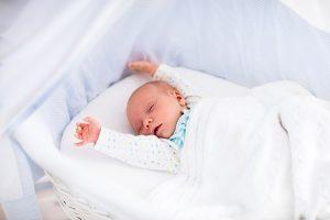 Baby mit Moro-Reflex streckt Ärmchen in die Luft