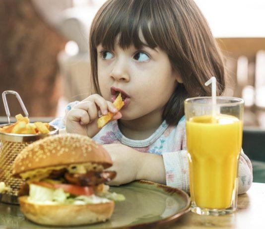 Kleines Mädchen isst Fast Food