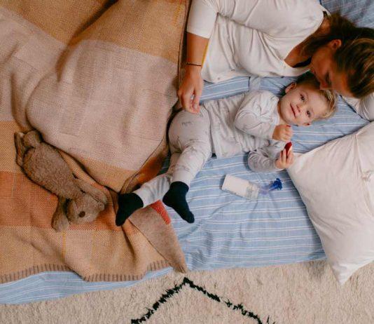 Kind krank mit Mama im Bett