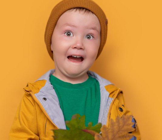Herbst mit Kindern: Junge in Regenzeug schneidet Grimasse
