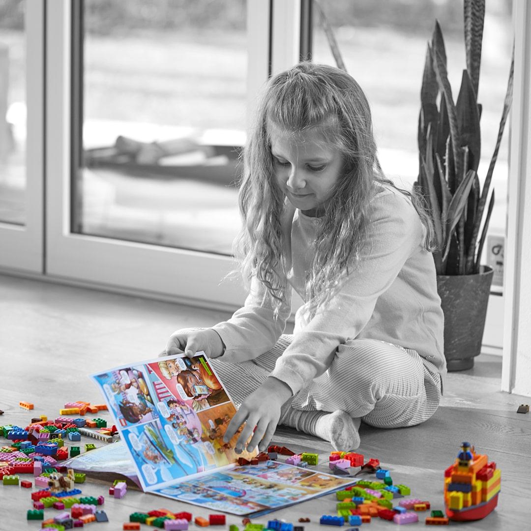 Mädchen liest LEGO Life Magazin