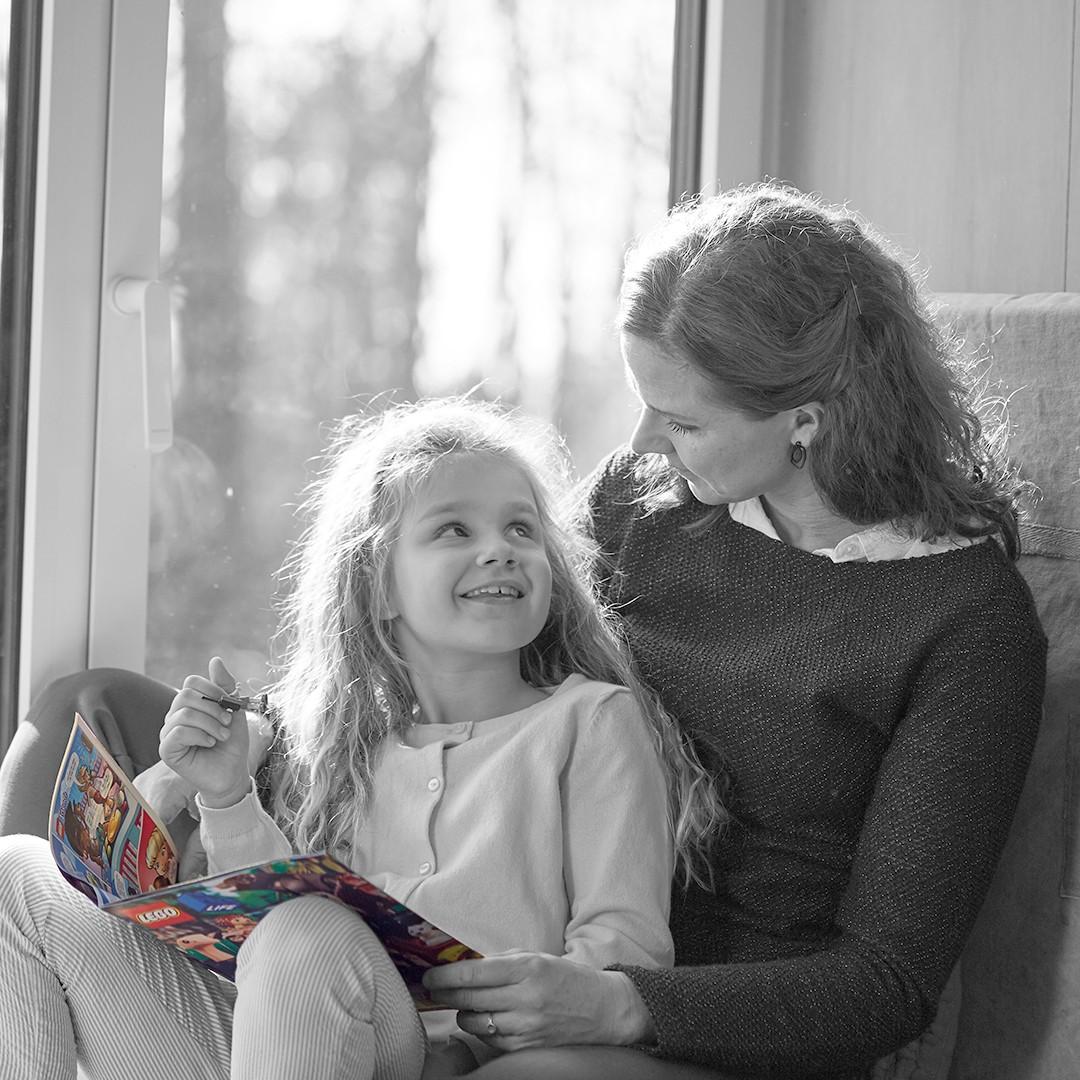 Mama und Tochter lesen und kuscheln.