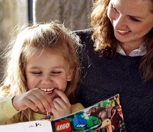 Spielen mit Kindern: Mama und Tochter lesen LEGO Life Magazin.