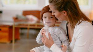 Kind beim Inhalieren mit dem Inhalationsgerät von OMRON